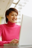 Young woman using laptop, smiling - Alex Microstock02
