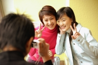 Young man holding camera, two women posing for picture, making peace sign - Alex Microstock02