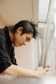 Young man using mobile phone, leaning on railing - Alex Microstock02