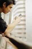 Young man using mobile phone, sideview - Alex Microstock02