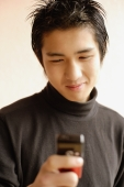 Young man using mobile phone, smiling - Alex Microstock02