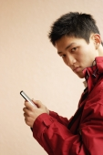 Young man holding mobile phone, looking at camera - Alex Microstock02