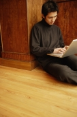 Young man using laptop, sitting on floor - Alex Microstock02