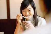Young woman holding bowl, eating soup - Alex Microstock02