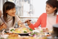 Young women eating at Chinese restaurant, side by side - Alex Microstock02