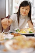 Young woman at a Chinese restaurant, eating - Alex Microstock02