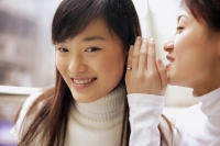 Young woman whispering to another woman - Alex Microstock02