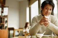 Young man sitting at table holding teacup - Alex Microstock02
