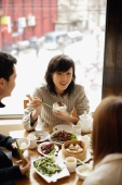 Young woman and friends at a Chinese restaurant - Alex Mares-Manton