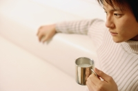 Young man sitting, holding coffee mug - Alex Microstock02
