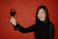 Woman holding up glass of wine, smiling - Alex Microstock02