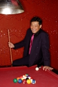 Man with pool cue leaning on table. - Alex Microstock02