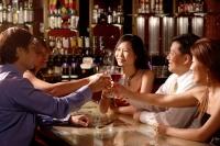 Group of people sitting around table toasting - Alex Microstock02