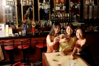 Three women holding wine glasses, looking at camera - Alex Microstock02