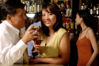 Couple having drinks, woman looking at camera - Alex Microstock02
