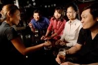Couples sitting at bar, bartender serving them - Alex Microstock02