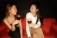 Two women with drinks sitting on sofa - Alex Microstock02