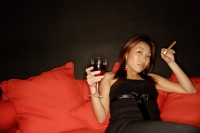 Woman holding wine glass and cigar, lying back on sofa - Alex Microstock02