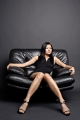 Young woman on black chair, looking at camera - Alex Microstock02