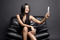 Young woman on black chair, looking at camera phone - Alex Microstock02