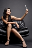 Young woman on chair holding camera phone - Alex Microstock02