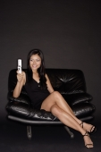 Young woman with mobile phone, sitting on black chair, smiling - Alex Microstock02