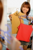 Young woman looking at mirror, holding clothes on hangers - Alex Microstock02