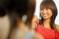 Young woman looking at mirror, holding up tank top - Alex Microstock02