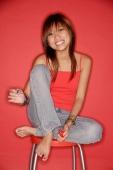 Young woman on stool holding nail polish bottle - Alex Microstock02