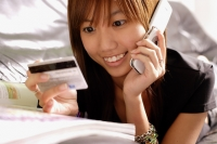 Young woman looking credit card, using phone - Alex Microstock02