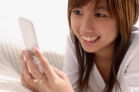 Young woman using mobile phone, text messaging - Alex Microstock02