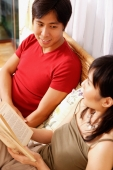 Couple on bed, side by side, woman with book - Alex Microstock02