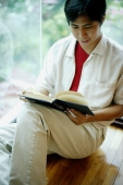 Man leaning on window, reading a book - Alex Microstock02
