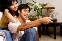 Couple at home, man holding remote control - Alex Microstock02