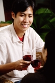 Couple toasting with wine glasses, man smiling - Alex Microstock02