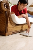 Man lying on sofa, using laptop resting on floor - Alex Microstock02