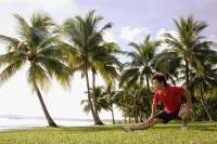 Man doing stretching exercises in park, hand on knee - Alex Microstock02
