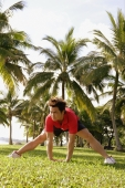 Man doing stretching exercises in park, bending forward - Alex Microstock02