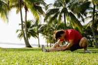 Man doing stretching exercises in park, leg outstretched - Alex Microstock02