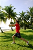 Man stretching in park, wearing red shirt - Alex Microstock02