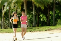 Two women jogging along beach, side by side - Alex Microstock02