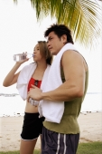 Couple standing at beach, side by side, woman drinking water - Alex Microstock02