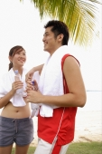 Couple standing at beach, side by side, holding water bottles - Alex Microstock02