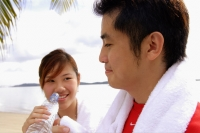Couple at beach, woman holding water bottle, man holding towel - Alex Microstock02