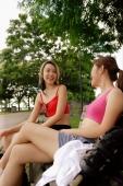 Two women sitting side by side on park bench, talking - Alex Microstock02