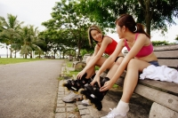Two women sitting side by side on park bench, putting on roller blades - Alex Microstock02