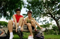 Two men on park bench, putting on roller blades - Alex Microstock02