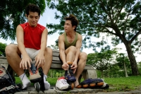 Two men on park bench, putting on roller blades, side by side - Alex Microstock02