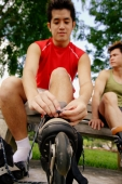One man putting on roller blades, the other looking away - Alex Microstock02