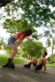 Couple inline skating at park, man on floor - Alex Microstock02